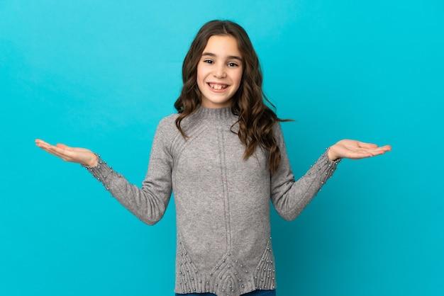 Mała dziewczynka kaukaski na białym tle na niebieskiej ścianie z zszokowanym wyrazem twarzy