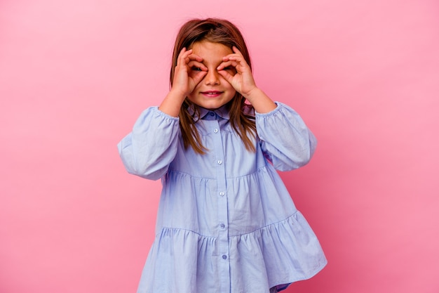 Mała dziewczynka kaukaski na białym tle na różowej ścianie pokazuje znak porządku na oczy
