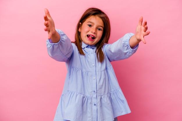 Mała dziewczynka kaukaski na białym tle na różowym tle czuje się pewnie, przytulając się do kamery.