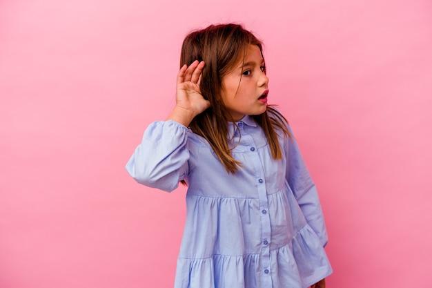 Mała dziewczynka kaukaski na białym tle na różowym tle próbuje słuchać plotek.