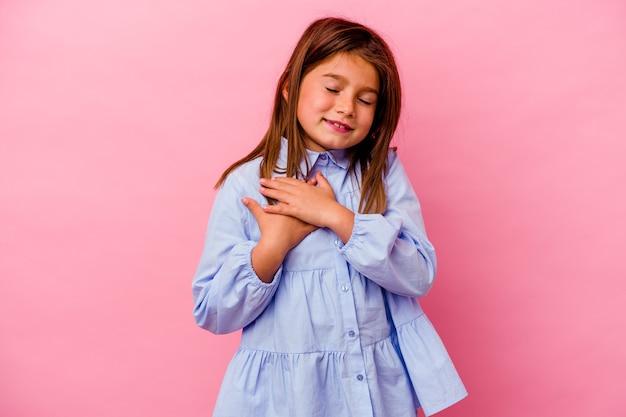 Mała dziewczynka kaukaski na białym tle na różowym tle śmiejąc się trzymając ręce na sercu, pojęcie szczęścia.
