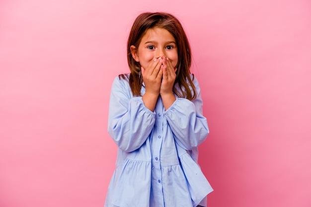 Mała dziewczynka kaukaski na białym tle na różowym tle śmiejąc się z czegoś, zakrywając usta rękami.