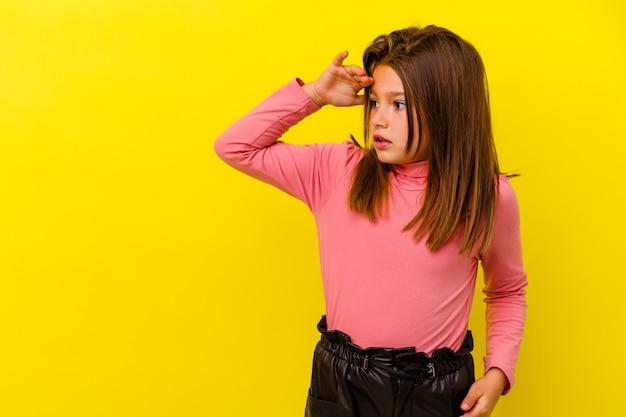 Mała dziewczynka kaukaski na białym tle na żółtym tle, patrząc daleko, trzymając rękę na czole.