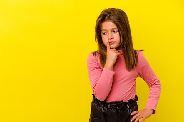 Mała dziewczynka kaukaski na białym tle na żółtym tle patrząc z boku z wyrazem wątpliwości i sceptyczny.