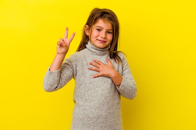 Mała dziewczynka kaukaski na białym tle na żółtym tle składa przysięgę, kładąc rękę na klatce piersiowej.