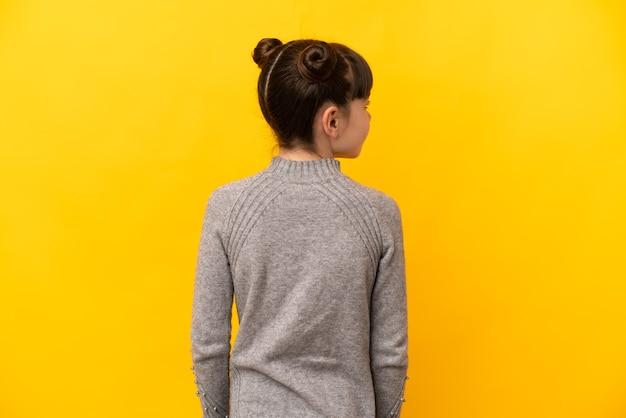 Mała Dziewczynka Kaukaski Na Białym Tle Na żółtym Tle W Tylnej Pozycji I Patrząc Z Boku Premium Zdjęcia