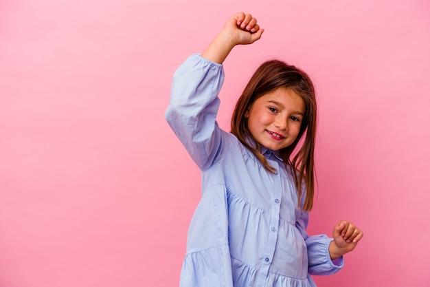 Mała dziewczynka kaukaski na różowej ścianie świętuje specjalny dzień, skacze i podnosi ręce z energią.