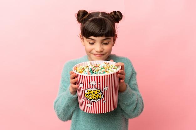 Mała dziewczynka kaukaski na różowej ścianie trzyma duże wiadro popcorns