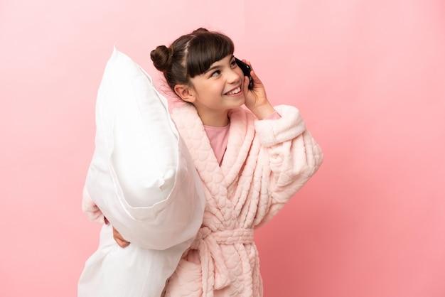 Mała dziewczynka kaukaski na różowej ścianie w piżamie i trzymając poduszkę podczas rozmowy z telefonem komórkowym