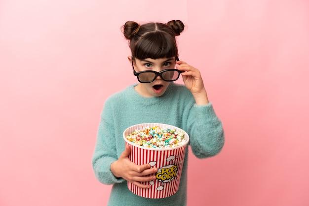 Mała dziewczynka kaukaski na różowej ścianie zaskoczona okularami 3d i trzymająca duże wiadro popcornu