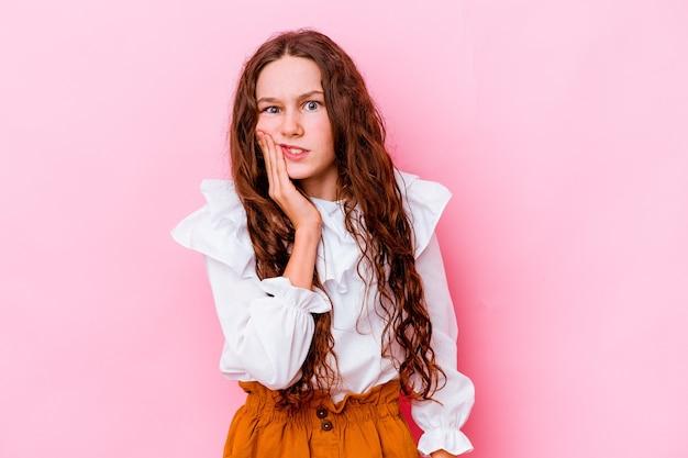Mała dziewczynka kaukaski na różowym tle o silnym bólu zębów, bólach trzonowych.