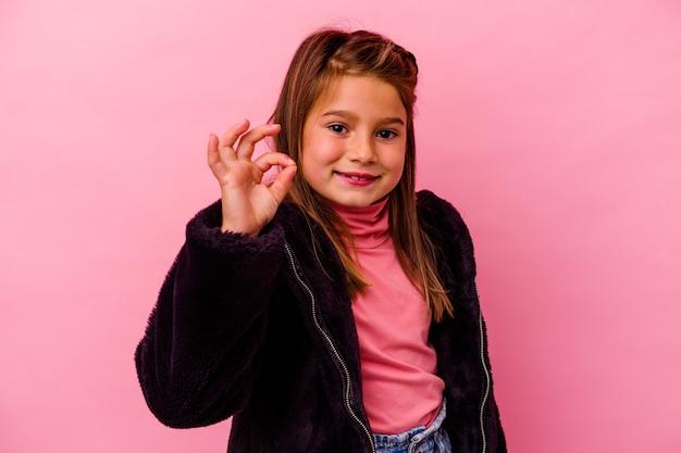 Mała dziewczynka kaukaski na różowym tle wesoły i pewny siebie, pokazując ok gest.