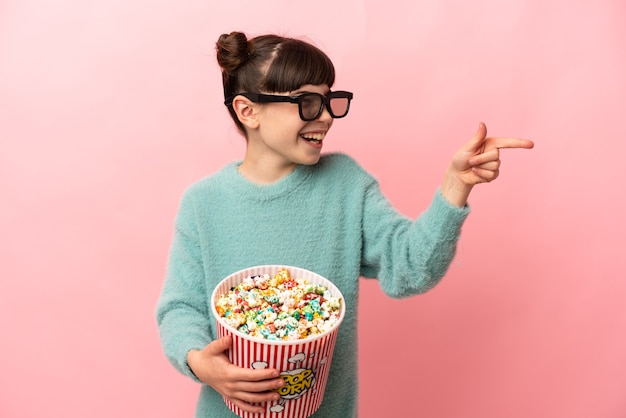 Mała dziewczynka kaukaski na różowym tle z okularami 3d i trzymając duże wiadro popcorns, wskazując przód