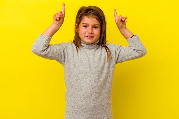 Mała dziewczynka kaukaski na żółtej ścianie wskazuje obiema palcami przednimi do góry, pokazując puste miejsce.