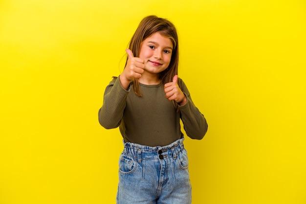 Mała dziewczynka kaukaski na żółtym tle, podnosząc oba kciuki do góry, uśmiechnięta i pewna siebie.