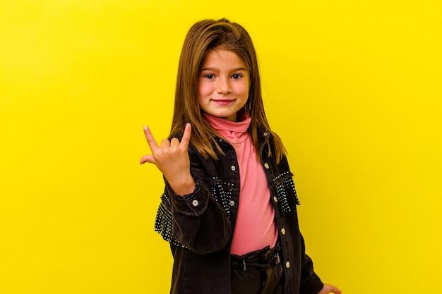 Mała dziewczynka kaukaski na żółtym tle pokazując rockowy gest palcami