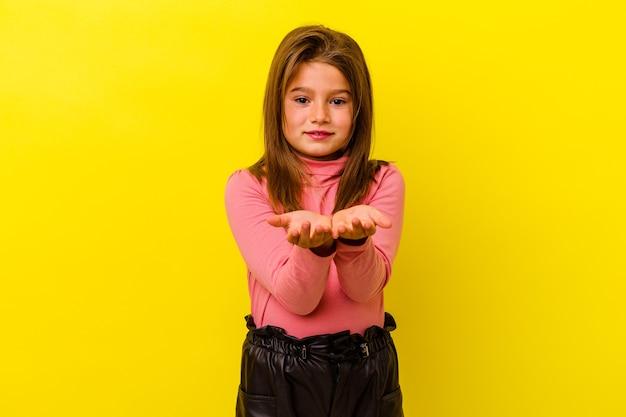 Mała dziewczynka kaukaski na żółtym tle trzyma coś z palmami, oferując do aparatu.