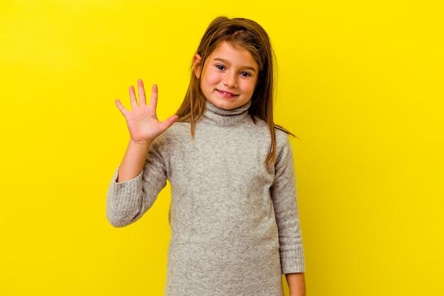 Mała dziewczynka kaukaski na żółtym tle uśmiechnięty wesoły pokazując numer pięć palcami.
