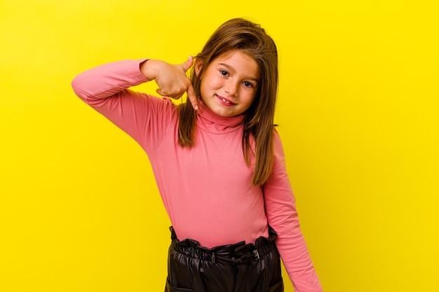 Mała dziewczynka kaukaski na żółtym tle wskazując ręką na przestrzeni kopii koszuli, dumny i pewny siebie
