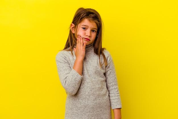 Mała dziewczynka kaukaski odizolowana na żółto o silnym bólu zębów, bólach trzonowych.