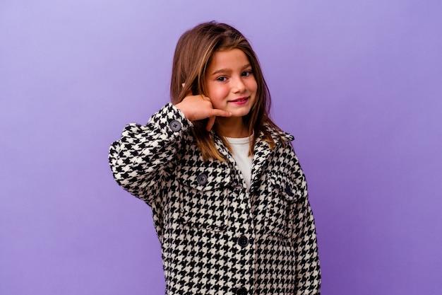 Mała dziewczynka kaukaski samodzielnie na fioletowym tle mała dziewczynka kaukaski samodzielnie na fioletowym tle pokazujący gest połączenia telefonu komórkowego palcami.