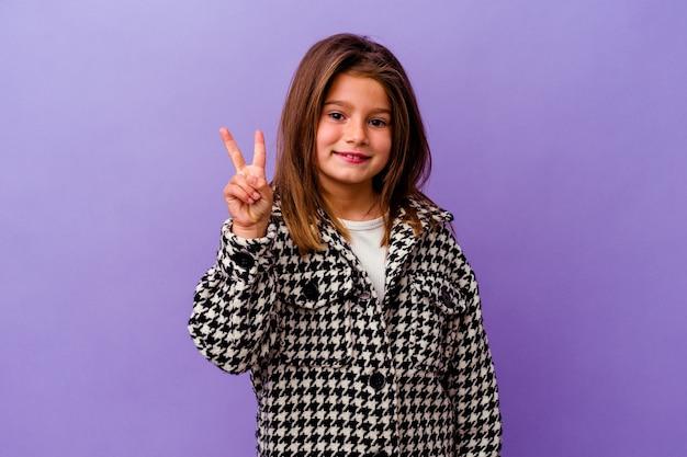 Mała dziewczynka kaukaski samodzielnie na fioletowym tle mała dziewczynka kaukaski samodzielnie na fioletowym tle radosny i beztroski pokazując symbol pokoju palcami.