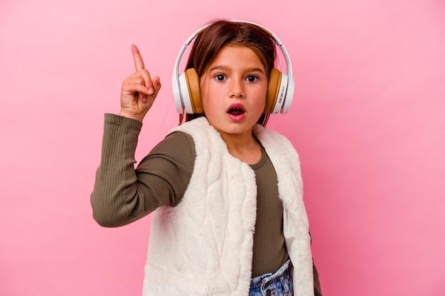 Mała dziewczynka kaukaski słuchanie muzyki na białym tle na różowej ścianie, mając pomysł, koncepcja inspiracji.