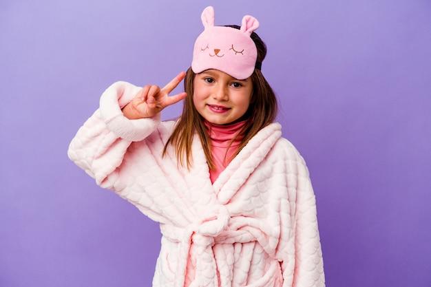 Mała dziewczynka kaukaski sobie piżamę na białym tle na fioletowej ścianie pokazuje numer dwa palcami.