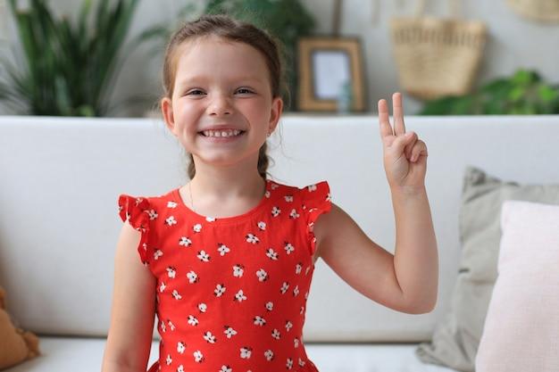 Mała dziewczynka kaukaski w czerwonej sukience siedzi na kanapie, uśmiechając się z uśmiechniętą twarz robi znak zwycięstwa.