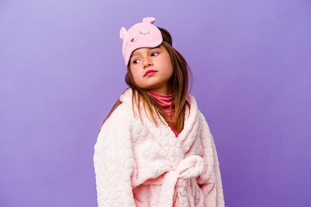 Mała dziewczynka kaukaski w piżamie na białym tle na fioletowej ścianie marzy o osiągnięciu celów i zamierzeń