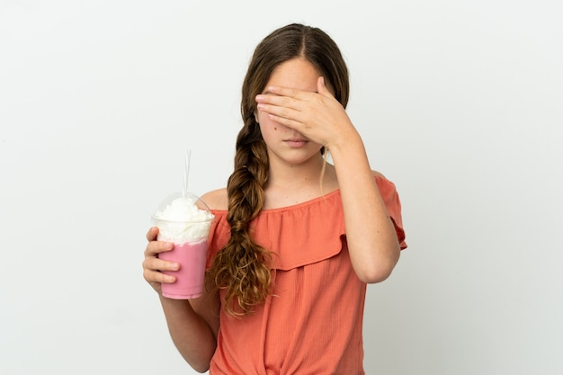 Mała dziewczynka kaukaski z truskawkowym koktajlem mlecznym na białym tle zasłaniając oczy rękami. nie chcę czegoś widzieć