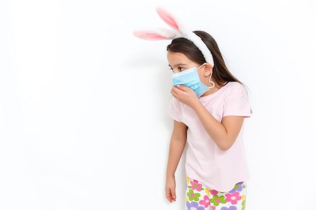 Mała dziewczynka kaukaski z uszami królika i maską medyczną na twarzy na białym tle. koncepcja wielkanocy. ochrona przed koronawirusem
