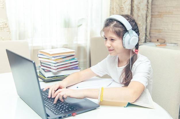 Mała dziewczynka kaukaski ze słuchawkami oglądając film instruktażowy na komputerze. nauka online na komputerze, koncepcja nauczania w domu.