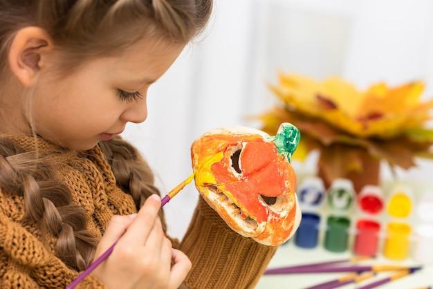 Mała dziewczynka koloruje dynie na zabawne przyjęcie na halloween.