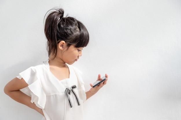 Mała dziewczynka koncentruje się na telefonie, spójrz na smartfon, koncepcja technologii dla dzieci, widok profilu, izolowana na białym tle, skopiuj miejsce