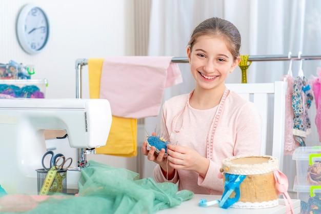 Mała dziewczynka krawiec pracuje z maszyną do szycia
