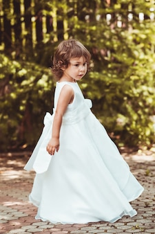Mała dziewczynka kręci się w ozdobnej sukience na świeżym powietrzu