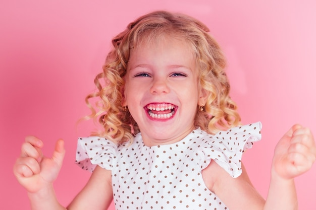 Mała dziewczynka królowa piękności niebieskie oczy, loki blond fryzurę z koroną tiara na głowie w uroczej bieli. sukienka w groszku pozuje w studio na różowym tle.obchody urodzin,konkurs piękności