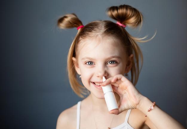 Mała dziewczynka kropi sprayem do nosa