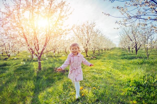 Mała dziewczynka, która biegnie między kwitnącymi drzewami o zachodzie słońca. ar
