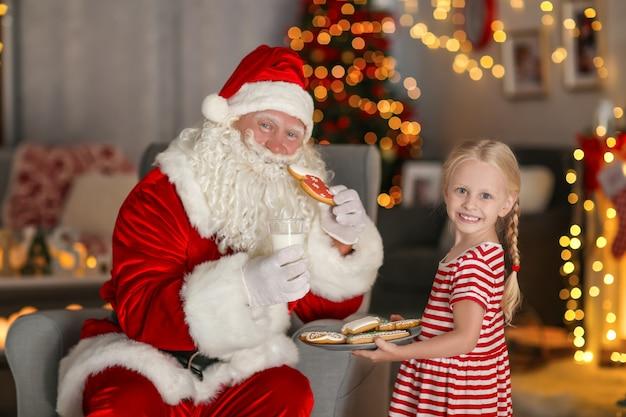 Mała dziewczynka leczy świętego mikołaja smacznymi ciasteczkami i mlekiem w pokoju z pięknymi dekoracjami świątecznymi