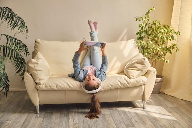 Mała dziewczynka leżąc do góry nogami na kanapie i bawić się tabletem