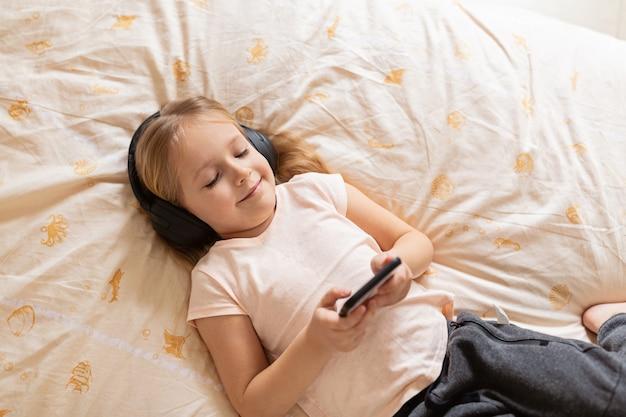 Mała dziewczynka leżąc na łóżku z bezprzewodowymi słuchawkami i telefonem