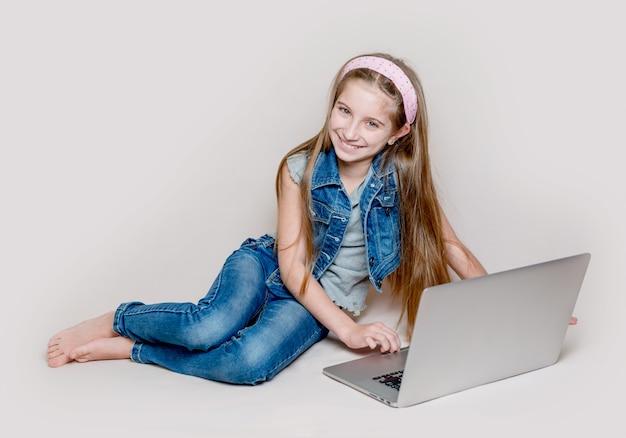 Mała dziewczynka leżąc na podłodze z laptopem