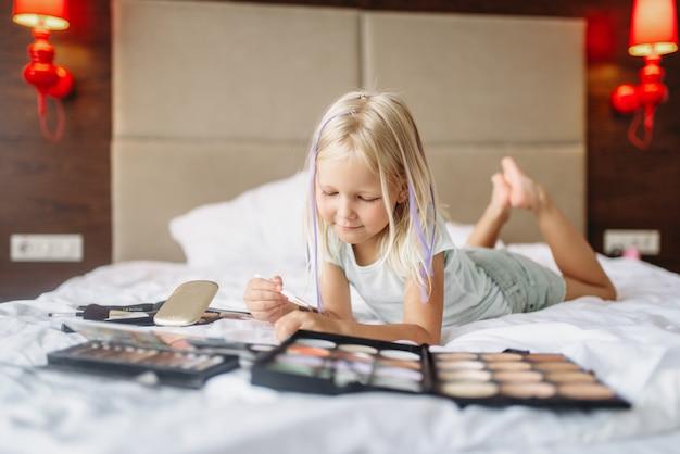 Mała dziewczynka leżąc w łóżku i bawić się makijażem mamy w domu. prawdziwie beztroskie dzieciństwo, szczęśliwy czas