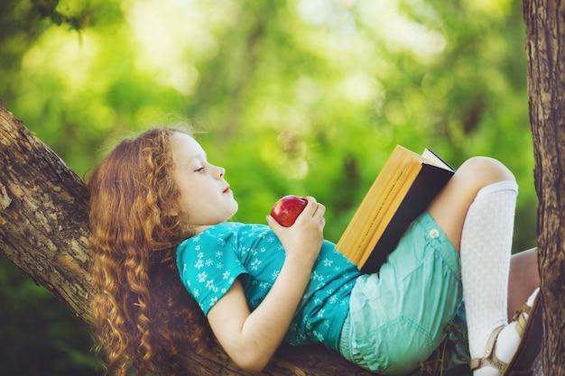Mała dziewczynka leży na dużym drzewie i czyta książkę.