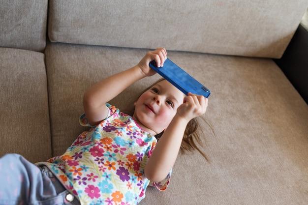 Mała dziewczynka leży na kanapie i patrzy na telefon