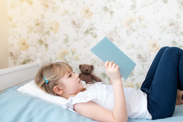 Mała dziewczynka leży na łóżku w stylowej sypialni i czyta niebieską książkę, odrabiając lekcje. edukacja, koncepcja nauczania w domu