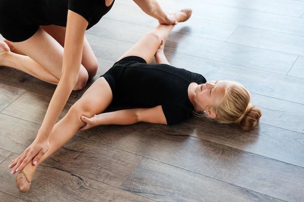 Mała dziewczynka leży na podłodze i robi ćwiczenia rozciągające ze swoim nauczycielem w studio