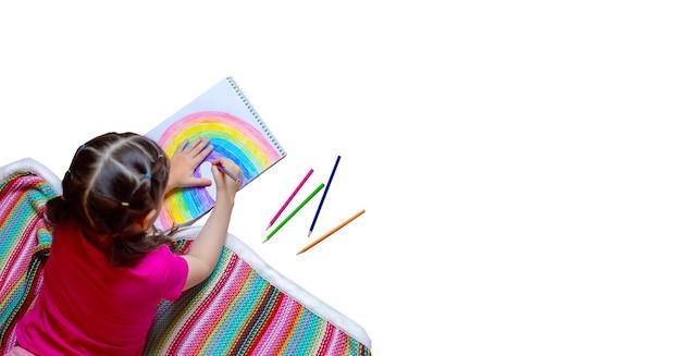 Mała dziewczynka leży na podłodze na kocu w kolorowe paski i rysuje tęczę